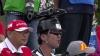 японский болельщик с каской сверху которой макет болида